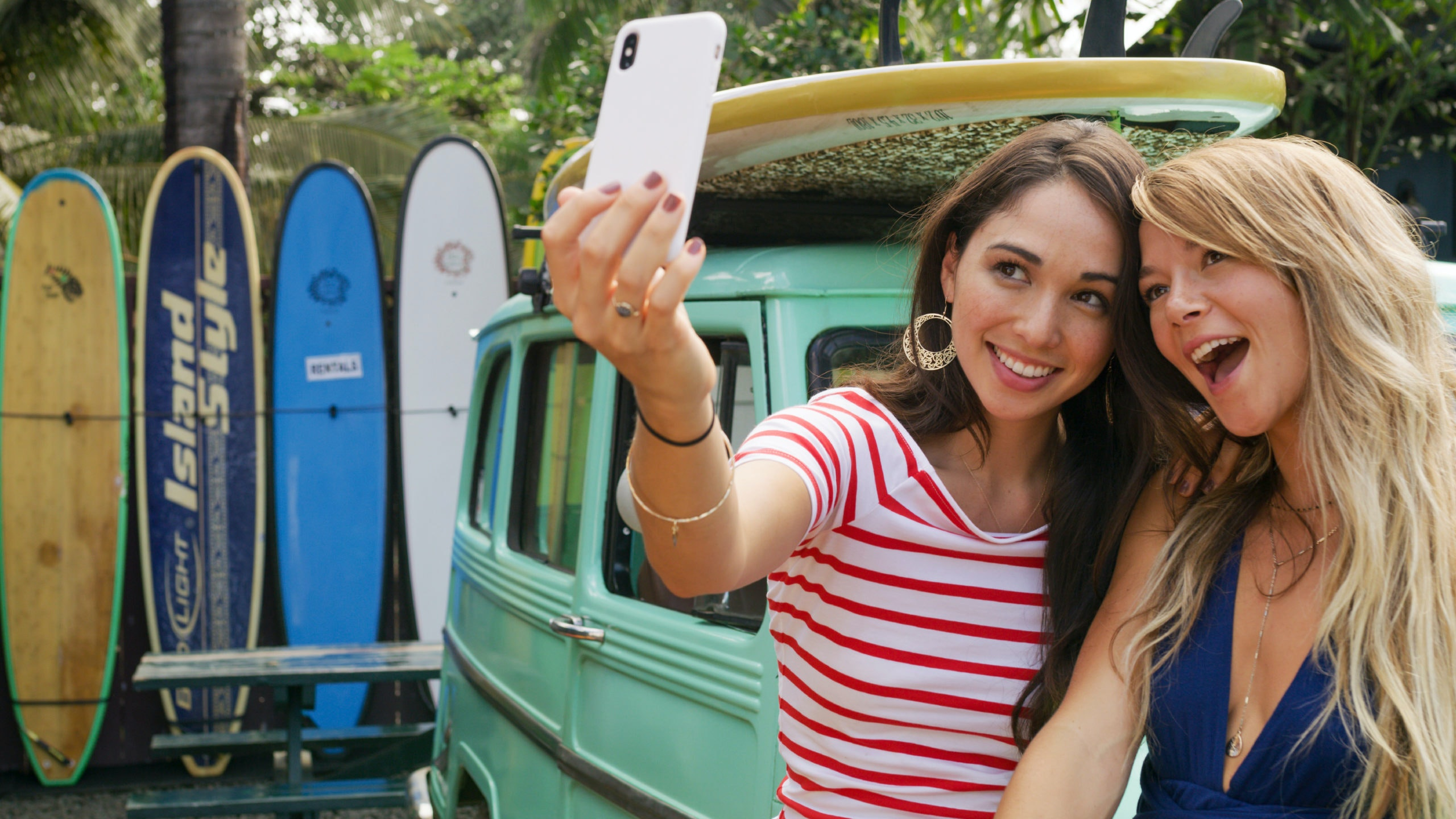 Two women standing in front of van and surfboards take a selfie