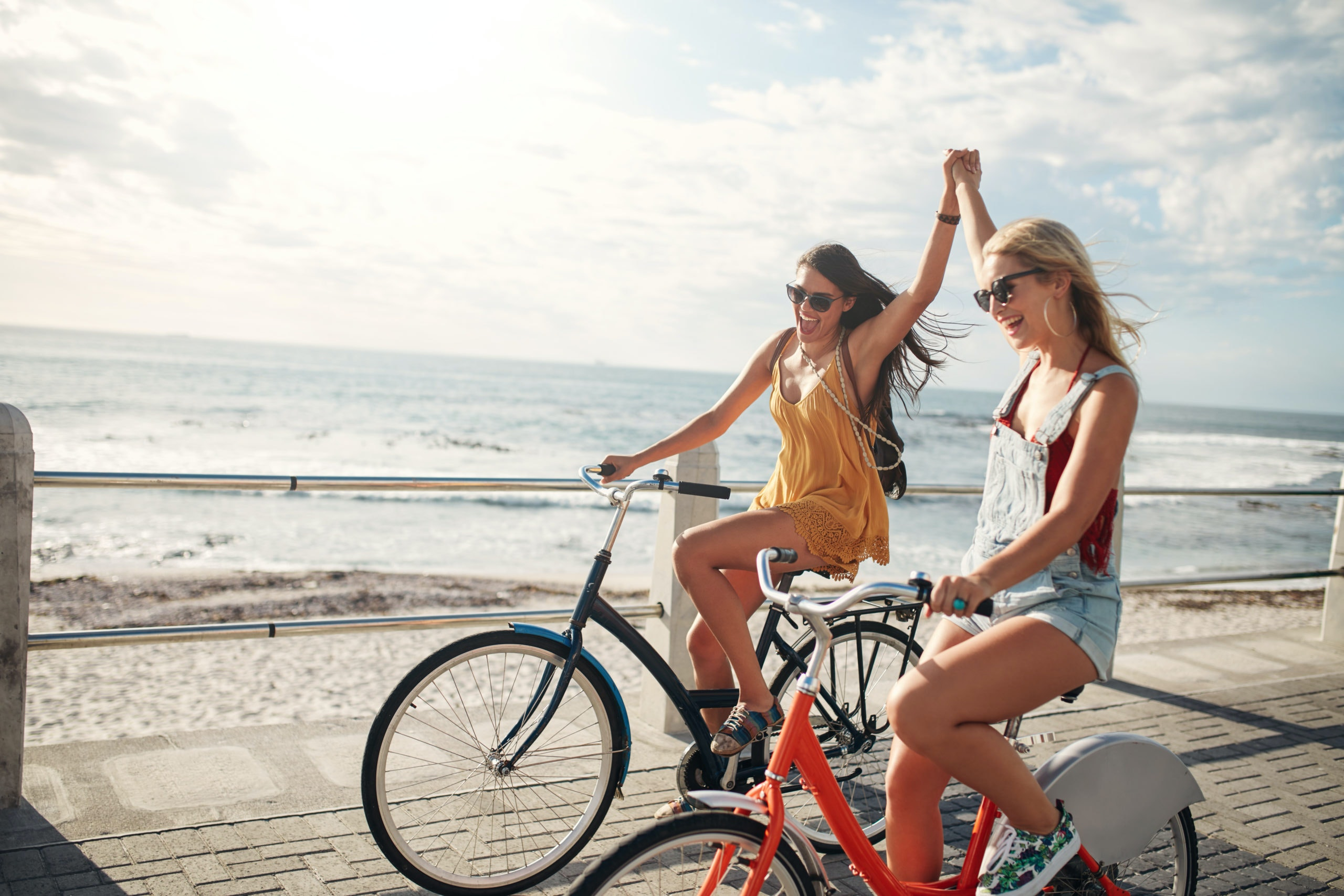 Two girls riding bikes by the beach